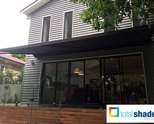 folding arm awning retractable shade over a deck overhead shade black cool in summer sun protection total shade solutions brisbane north moreton bay